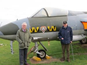 74 Tiger Squadron pilots David Jones and John Atkinson standing in front of a Hawker Hunter at City of Norwich Aviation Museum, in 74 Squadron markings